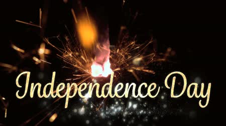 escrita : Digital animation of gold Independence Day text with bokeh lights while a lighted sparkle flickers in the dark background for fourth of July.