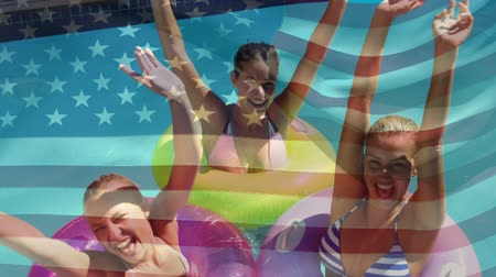 spangled : Digital composite of Caucasian women using colorful floaters in the pool lifting their arms while an American flag waves in the background for fourth of July.