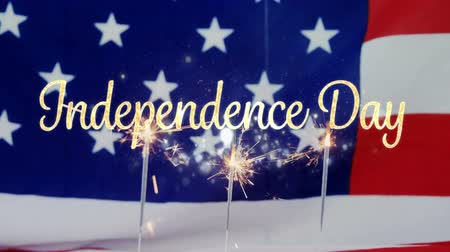spangled : Digital animation of a gold Independence day text appearing while background shows an American flag behind cupcakes with lighted sparkles flickering on top of a red and white table cloth for fourth of July. Stock Footage