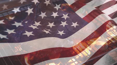 gurur : Digital composite of a meat barbecue on a fire grill while the American flag waves in the background for fourth of July. Stok Video