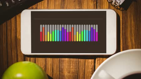 dane : Digital animation of a smartphone with a colourful bar graph on its screen. The phone is on a wooden table.