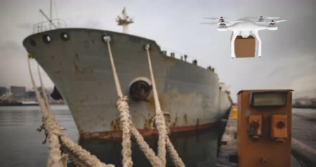 warehouses : Digital animation of a white drone carrying a brown box and hovering beside a ship in a port