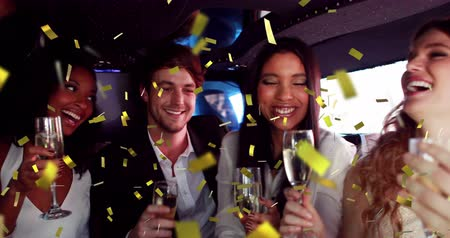 champagne flute : Digital composite of a group of diverse friends inside a limousine celebrating with glasses of champagne while gold confetti fall in the screen