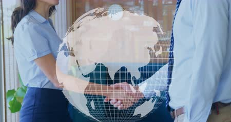 evrensel : Digital composite of a Caucasian business man and woman shaking hands inside an office while a digital globe rotates in the foreground