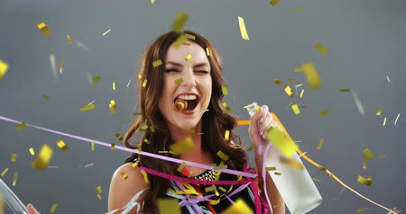 champagne flute : Digital composite of a Caucasian woman holding a glass and a bottle of champagne dancing and celebrating while party strings and gold confetti falling in the screen Stock Footage