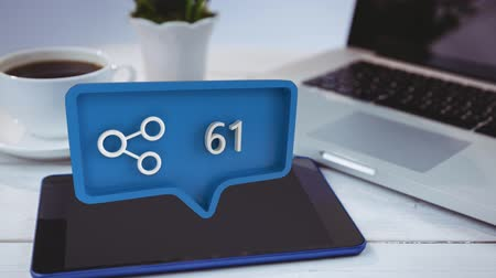 уведомление : Digital composite of a connect icon with increasing count in a message bubble. The bubble is pointing at a tablet beside a laptop and a cup of coffee for social media