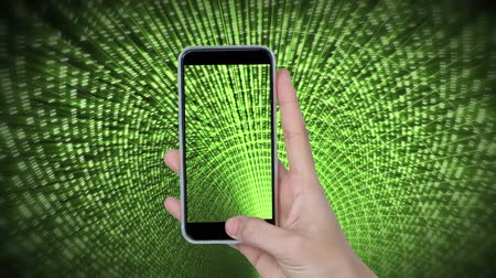 タイプスクリプト : Digital composite of a hand holding a mobile phone while screen and background shows a green matrix of binary codes zooming in the screen 動画素材