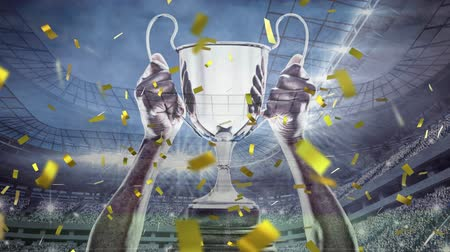 гонка : Digital animation of a hand holding a big trophy while gold confetti fall in the screen and background shows a filled stadium