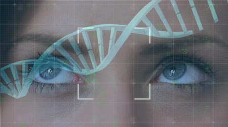 atomový : Digital animation of a DNA double helix rotating in the screen while background shows the eyes of a Caucasian woman looking around