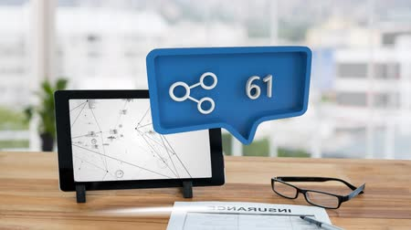 beside : Digital animation of a blue message bubble with a connection icon beside increasing numbers for social media. Background shows a wooden table with an eyeglass and a tablet with different graphs and lines on the screen Stock Footage