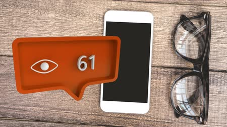 diváků : Digital animation of an orange message bubble with a view icon and increasing numbers for social media. Background shows a wooden desk with a mobile phone and eyeglass.