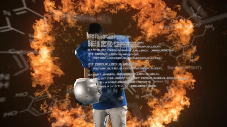 żródło : Digital composite of an African-American football player wearing a helmet while a fire explodes behind him. Chemical structures and program codes move in the foreground. Wideo