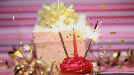 doğum günü : Digital composite of a lighted candle and sparkles on a cupcake sparkling with a gift in the background and gold confetti falling