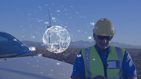 renovável : Digital composite of a Caucasian engineer in uniform using a tablet with a wind turbine in the background while a digital globe surrounded by numbers rotating in the screen