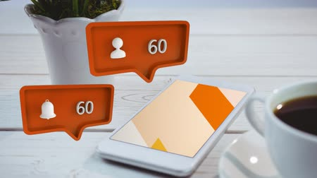 уведомление : Digital animation of an orange message bubble with a profile and notification icons and increasing numbers for social media. Background shows a wooden table with a pot and a mobile phone beside a cup of coffee. Стоковые видеозаписи