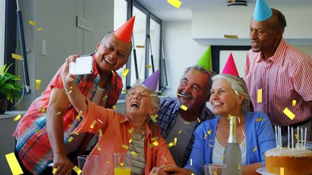 fondness : Digital composite of a group of old diverse friends taking a picture with a cellphone while celebrating a birthday and wearing party hats. Gold confetti fall in the foreground.