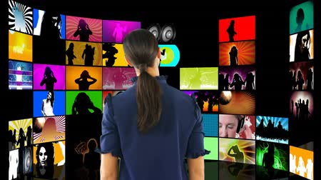 tv screen : Digital composite of a woman with back turned watching videos on LCD screens Stock Footage