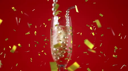 champagne flute : Digital composite of a glass of champagne with a pearl necklace against a red background while gold confetti fall in the screen