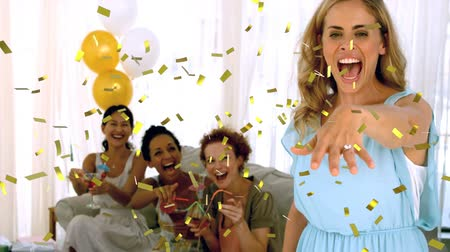 templombúcsú : Digital composite of a Caucasian woman showing off her engagement ring with diverse friends sitting in the background and gold confetti fall in the screen. Stock mozgókép