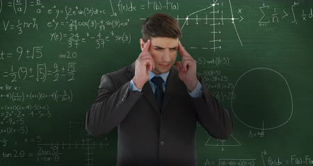 matemático : Animation of confused Caucasian man seen waist up standing holding his temples in front of moving mathematical graphs and formulae written in chalk on a chalkboard 4k