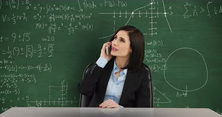 matemático : Animation of a young smiling Caucasian woman seen waist up sitting at a desk talking on smartphone. Behind her is a green chalkboard with moving mathematical calculations written in chalk 4k