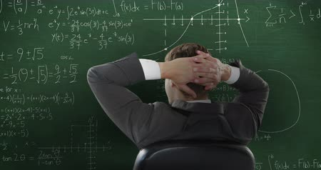matemático : Animation of Caucasian man sitting in front of chalkboard with moving mathematical graphs and formulae written in chalk 4k Stock Footage