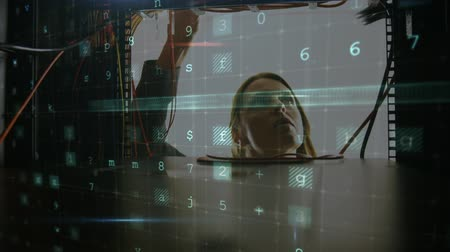 beheerder : Animation of a Caucasian woman working on computer server seen close up from inside the server rack, while glowing digital text about computer security flashes and moves in the foreground Stockvideo