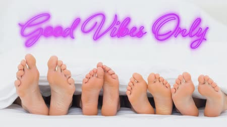 positive vibes : Animation of the words Good Vibes Only in handwriting style flickering pink neon, on a white background above a row of feet with soles facing the camera, belonging to four people that are lying down