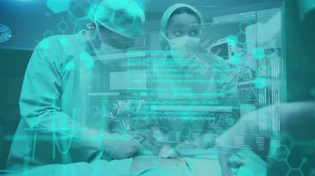 médicos : Animation of a team of surgeons operating on a patient in an operating theatre, seen waist up and in mid section, while glowing blue data and diagrams move in the foreground Stock Footage
