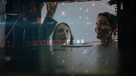 beheerder : Animation of a Caucasian woman and man working in computer server room seen close up from inside the server rack, while glowing digital text about computer security flashes and moves in the foreground Stockvideo