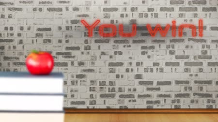 сосредоточиться на переднем плане : Animation of the words You Win! in flickering red neon effect letters on an exposed brick wall in a room, with a red apple on a pile of books, defocussed in the foreground