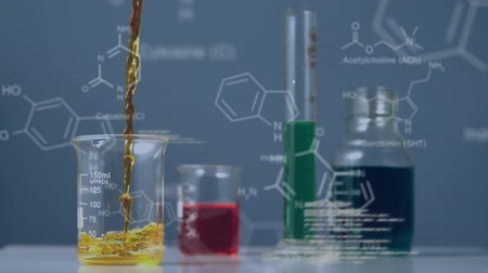 deney şişesi : Animation of yellow liquid pouring into a beaker standing with other measuring flasks containing coloured liquids on a laboratory bench, while scientific data and diagrams in white move in front and behind