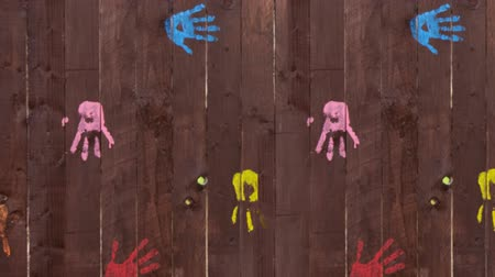 újra : Animation of pink and purple paint covering colourful painted handprints on wooden boards, and removed to reveal them again Stock mozgókép