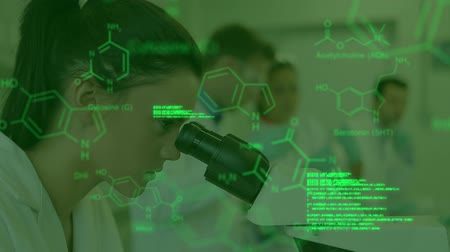 internar : Animation of green tinted head and shoulders side view of a female scientist using a microscope in a laboratory, with colleagues working in the background, while glowing green text and data moves in the foreground