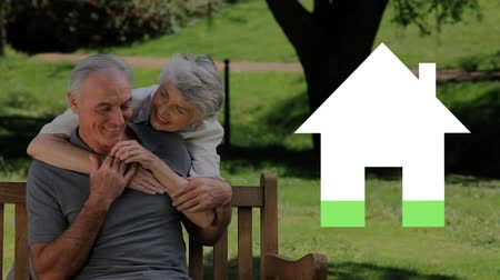 mülkiyet : Animation of a senior Caucasian couple sitting on a bench, embracing in a garden with an empty icon of a house filling with green