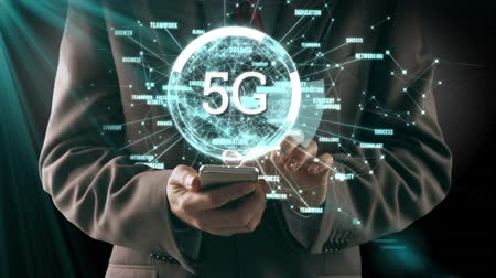 linked : Animation of 5g displayed in a rotating circle and spinning data while businessman is using smartphone in the background Stock Footage