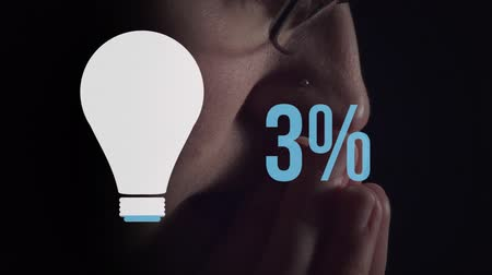 čtyřicátá léta : Animation of side view of young Caucasian thoughtful man wearing glasses with light bulb shape and percent increasing from zero to forty two filling in blue on black background Dostupné videozáznamy