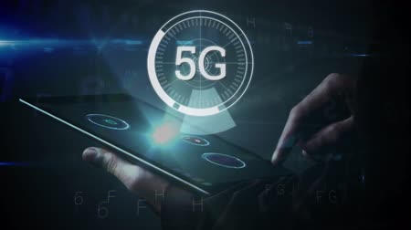 linked : Animation of 5g displayed in a rotating circle with data floating while a person uses tablet in the background Stock Footage