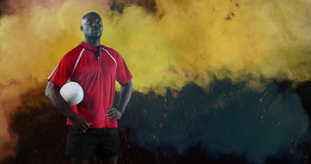 rugby ball : Animation of a young African American male rugby player looking around and holding a ball under his arm while colourful powder falls against a black background 4k