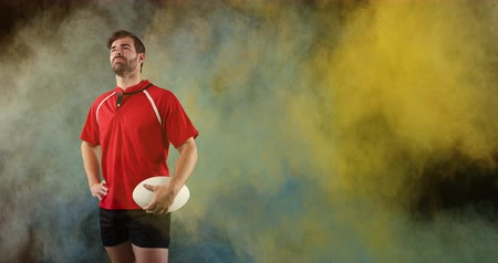 antecipação : Animation of a young Caucasian male rugby player looking around and holding a ball in his hand while colourful powder falls against a black background 4k