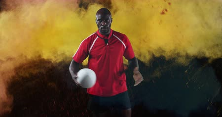 antecipação : Animation of a young African American male rugby player looking to camera, playing and pointing with a ball while colourful powder while colourful powder falls against a black background 4k