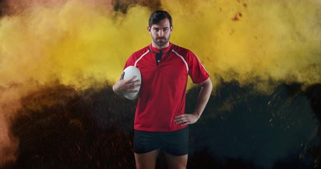rugby shirt : Animation of a young Caucasian male rugby player looking to camera and holding a ball in his hand while colourful powder falls against a black background 4k