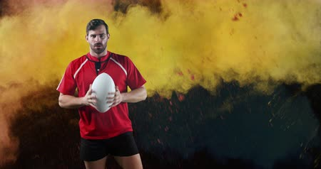 rugby shirt : Animation of a young Caucasian male rugby player standing, looking to camera and pointing with a ball while colourful powder falls against a black background 4k