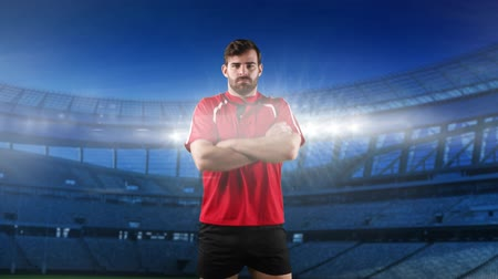 rugby shirt : Animation of a Caucasian male rugby player standing with arms crossed and looking to camera with floodlit stadium in the background