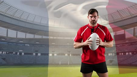 rugby shirt : Animation of a Caucasian male rugby player playing with a ball and looking to camera with blowing French flag and stadium in the background Stock Footage