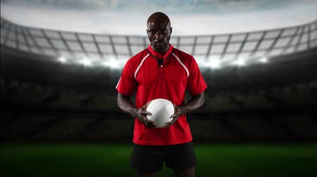 rugby shirt : Animation of an African American male rugby player playing with a ball and looking to camera with floodlit stadium in the background Stock Footage