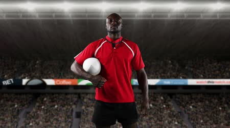antecipação : Animation of an African American male rugby player holding a ball and looking to camera with floodlit stadium in the background