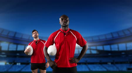 rugby shirt : Animation of an African American and a Caucasian male rugby player holding rugby balls and looking to camera with floodlit stadium in the background