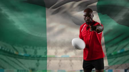 nigeria flag : Animation of an African American male rugby player playing with a ball and looking to camera with blowing Nigerian flag and stadium in the background
