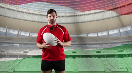 antecipação : Animation of a Caucasian male rugby player playing with a ball and looking to camera with blowing Hungarian flag and stadium in the background